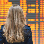 Woman looking at electronic departure board for canceled flight info