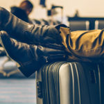 Men's feet resting on his suitcase while he is waiting for his delayed flight