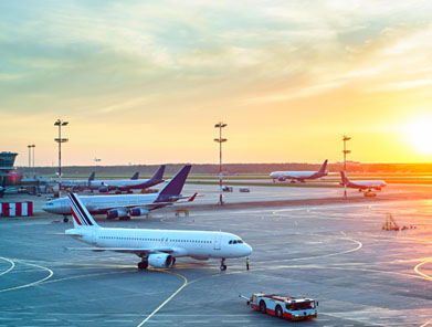Grounded airplanes on tarmac against the setting sun
