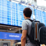 Man looking at flight departure board at airport