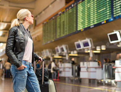 Woman looking at flight departure board at airport.