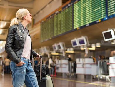 Woman looking at flight departure board at airport.