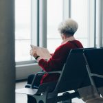 Grey haired woman sitting, waiting, and reading newspaper at airport waiting area.
