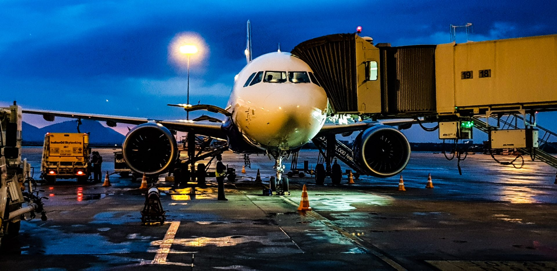 Delayed aircraft parked at gate against darkening sky background.