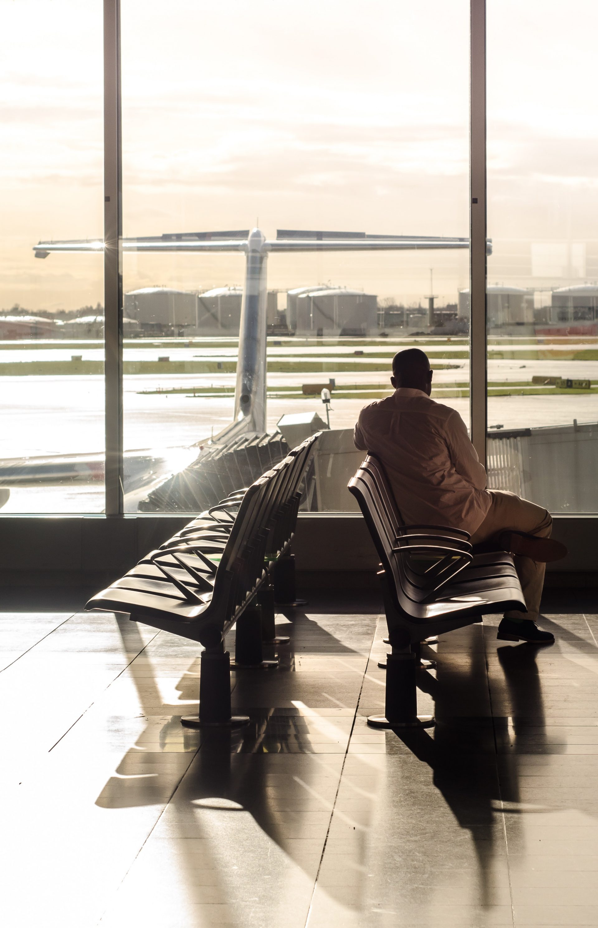 Man looking through window of airport at delayed aircraft by the gate