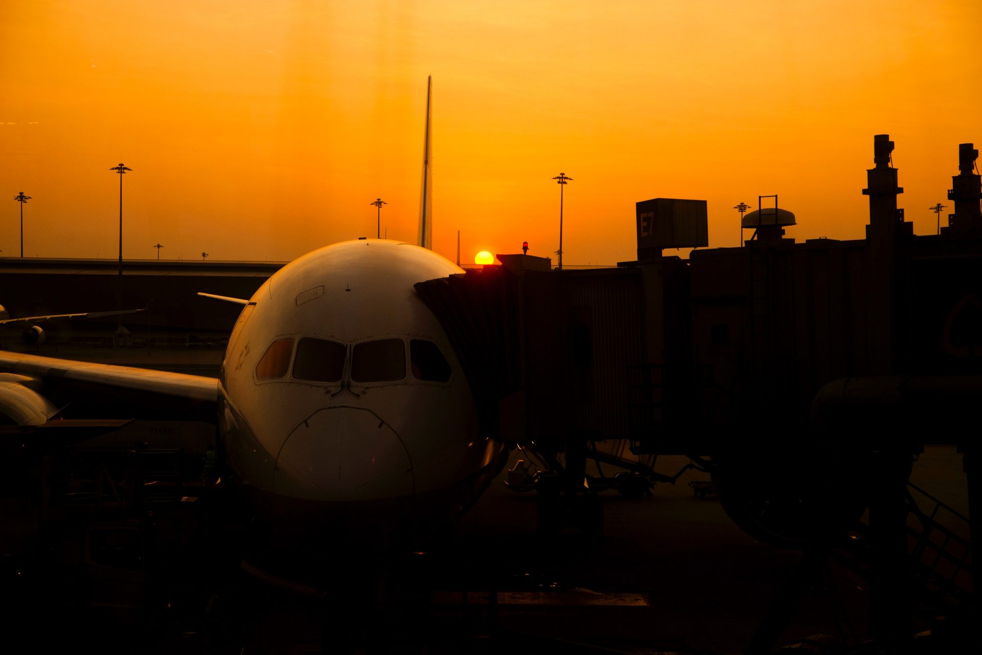 Delayed aircraft parked at gate with orange sky and sun setting in the background