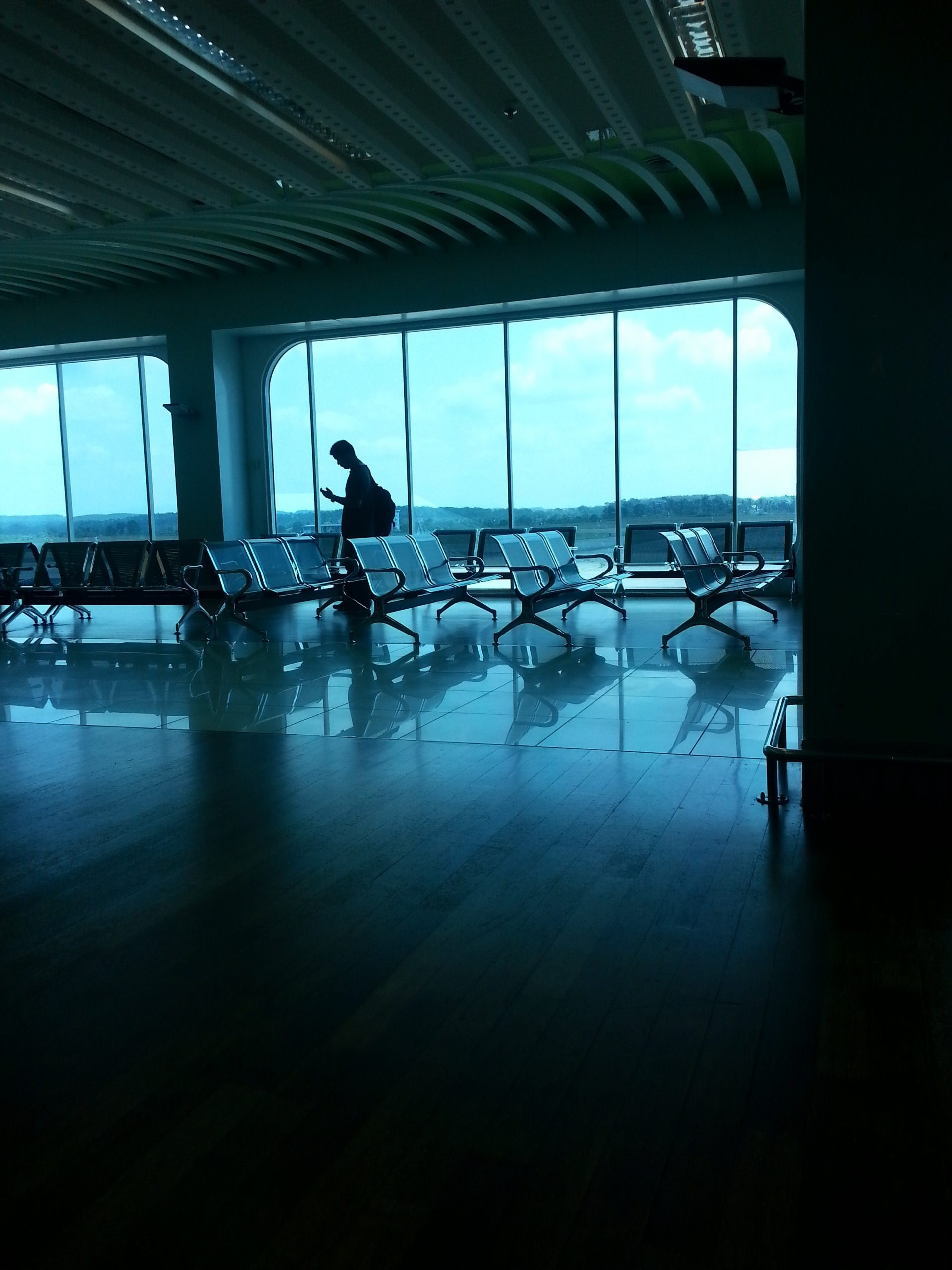 Silhouette of man walking in empty airport waiting area