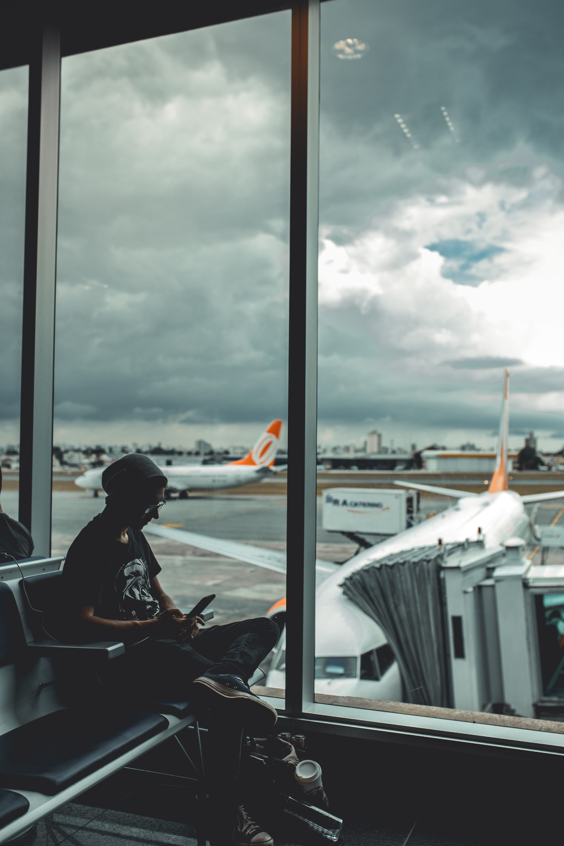 Person sitting at airport window with delayed flight in the background