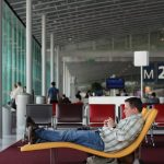 Man reclining at airport waiting area, checking phone for flight delays