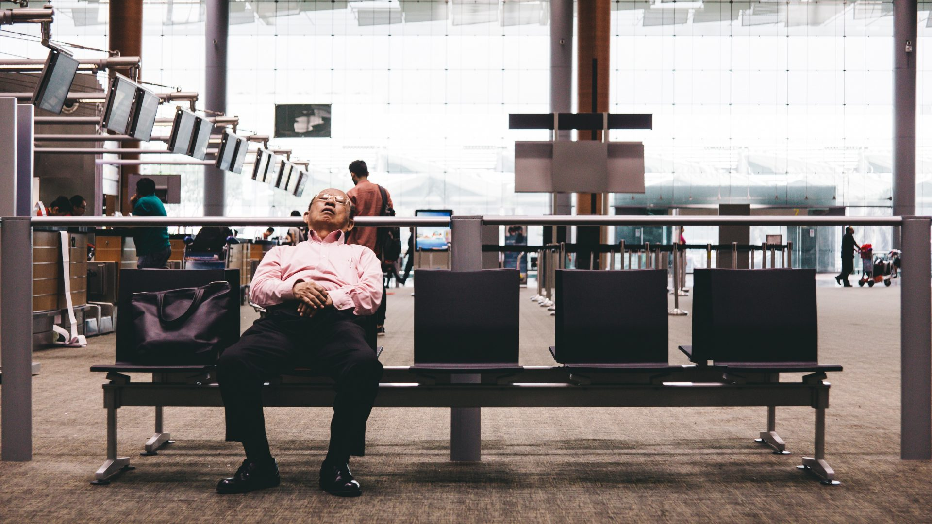 Older man sleeping at airport check in area, waiting for delayed flight