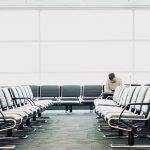 Man sitting alone at airport waiting area, checking phone for flight info