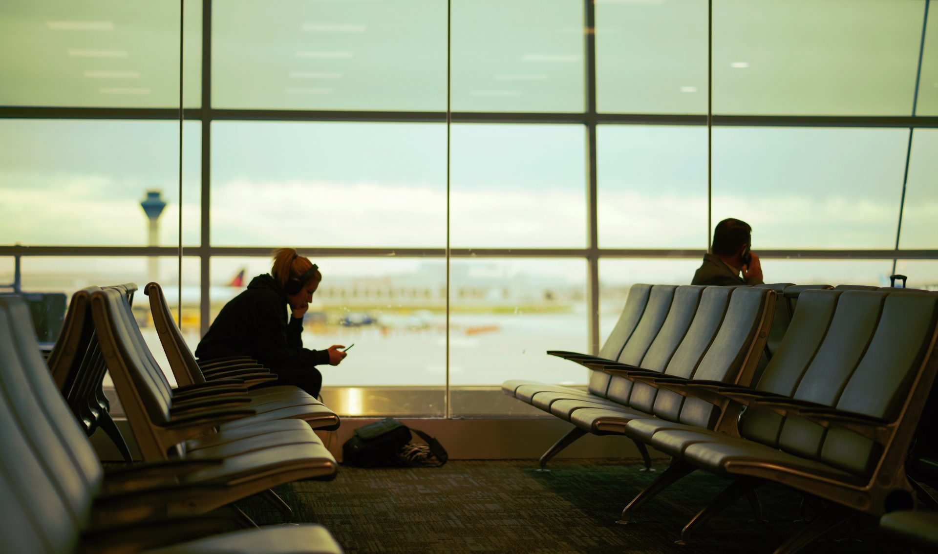 Sitting silhouettes against airport window, once checking phone for delayed flight info