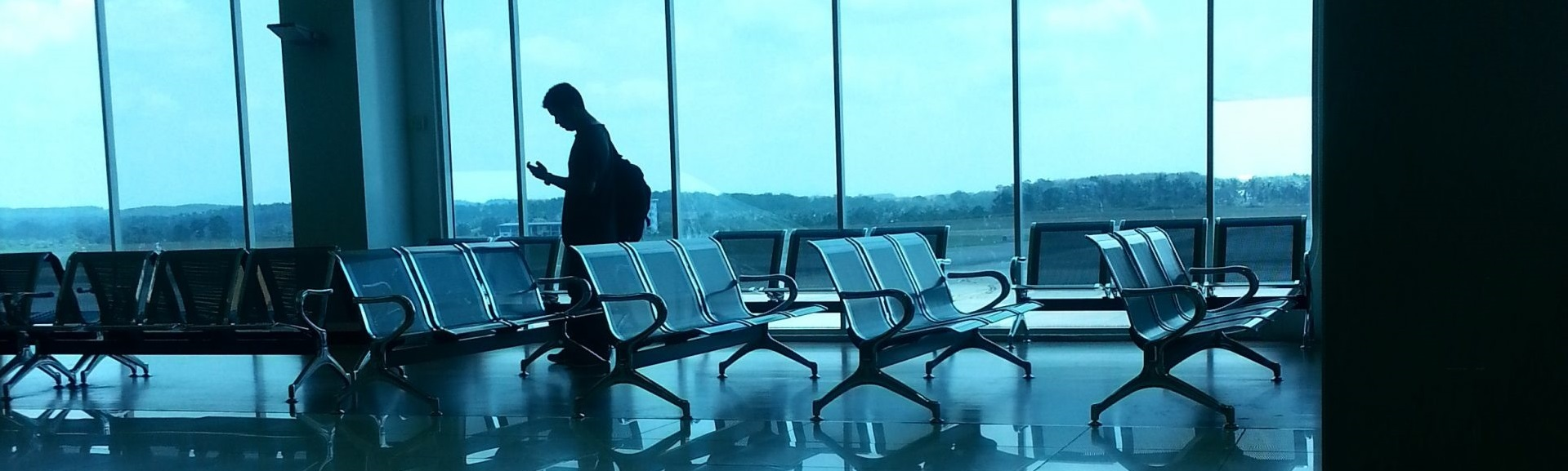 Man's silhouette walking by empty seats at airport